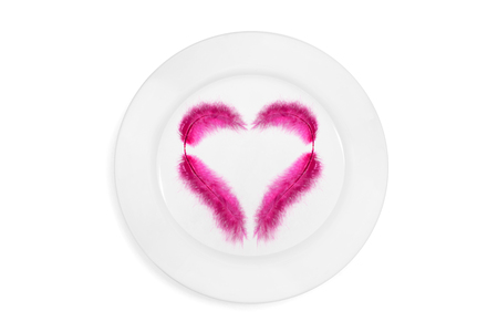 Top view on  a plate with pink feather in the heart shape on a white background. Concept of healthy and light food. Isolated