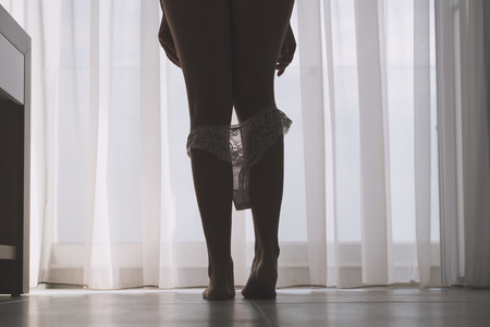 Bottom view of silhouette of beautiful woman with sexy legs taking off her white panties in a room against the backdrop of curtains Standard-Bild - 115532169