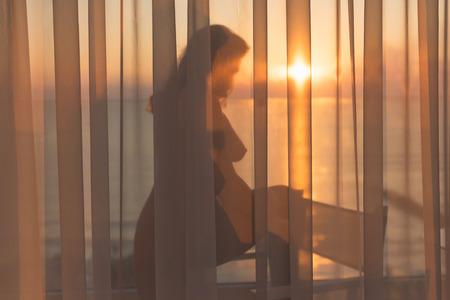 Belle fille nue se tient derrière le rideau transparent sur le balcon au lever du soleil sur la station balnéaire tropicale Banque d'images