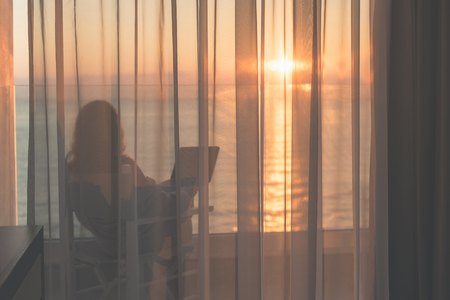 Naked beautiful female wrapped in a blanket sitting on a chair with laptop behind the transparent curtains on the glass balcony early morning at sunrise. Sea view