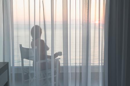 Belle femme nue assise sur une chaise avec une tasse de café derrière les rideaux transparents sur le balcon en verre tôt le matin au lever du soleil. Vue sur la mer