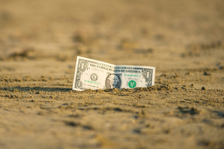 Banknote of value of one dollar in the the sand on the beach. Concept of cheap travel and vacation. Promotion and discount