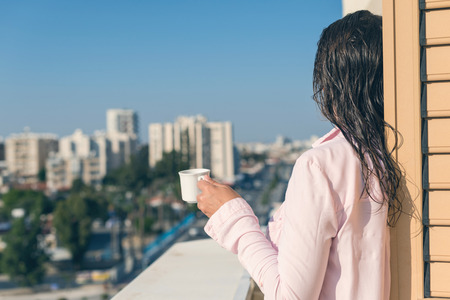 Woman with wet hear in a pink shirt with cup of coffee at the summer morning against the background of  town