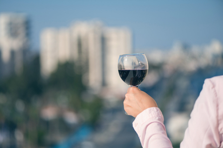 Woman hand with glass of wine against the background of town at summer evening 版權商用圖片