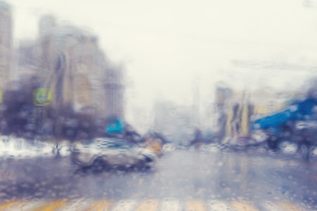 Blurred view through the windshield of a car with raindrops at a crossroad and pedestrian crossing. Stock Photo