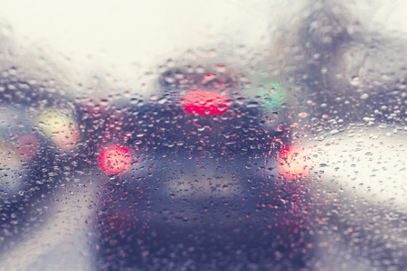Blurred view through the windshield of a car with raindrops on the stop signals car. Concept of drive safety on the road and speed limit Stock Photo