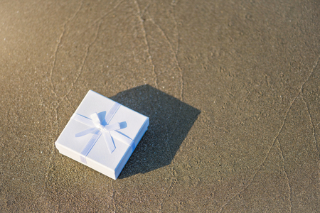 White gift box on the sand on a beach Imagens