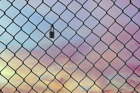 Conceptual image of twilight sky with effect of light pastel tone and steel mesh wire fence. Concept of hope and freedom 免版税图像