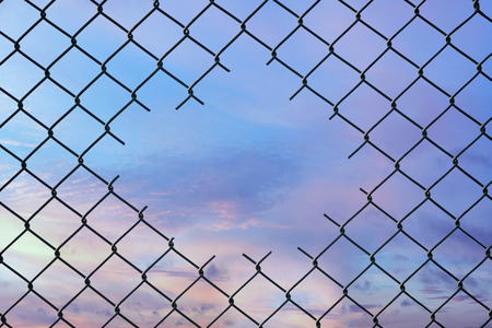 Hole in the center of mesh wire fence on the sky background. Concept of hope and freedom