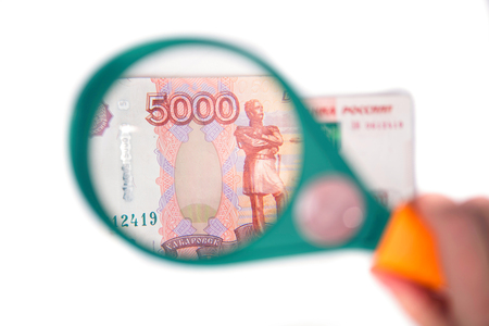 Banknote of five thousand russian rubles under a magnifying glass in the human hand. Concept Stock Photo