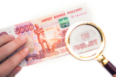 Banknote of five thousand russian rubles under a magnifying glass in the human hand. Concept Фото со стока