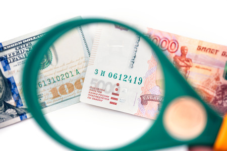 Five thousand russian rubles  under a magnifying glass on the backdrop euro and usa dollar. Ð¡oncept of the main international currency