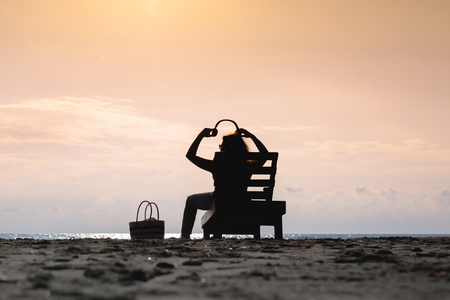 Girl in headphones is sitting on the sun lounger listening to music on the beach at sunset. Summer concept.