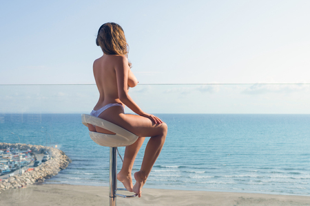 Naked woman in the headphones listening music sitting on a high chair on the balcony and looking on the sea and sky. Archivio Fotografico