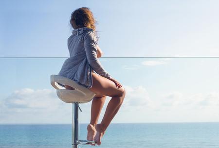 Mujer desnuda en la chaqueta sentada en una silla alta en el balcón y mirando al mar y al cielo. Foto de archivo