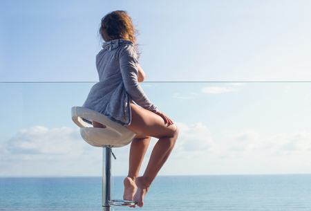 Naked woman in the jacket sitting on a high chair on the balcony and looking on the sea and sky. Standard-Bild