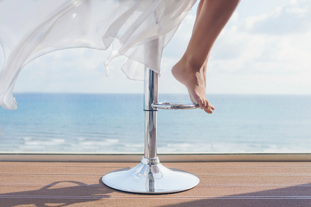 woman is sitting on a bar stool in a summer cafe on the sea and sky background. Bottom view on barefoot female legs