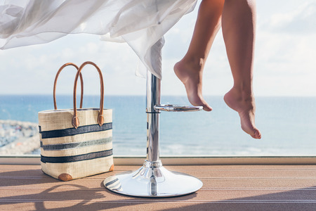 A girl with a beach bag is sitting on a bar stool in a summer cafe on the sea and sky background. Bottom view on barefoot female legs Banco de Imagens