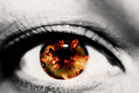 Double exposure of the closeup female eye and hot red coals from firewood in a fireplace