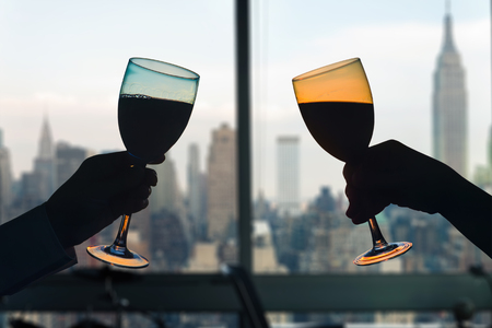 Man and female toasting with glasses of red wine in the apartment with New York city view.