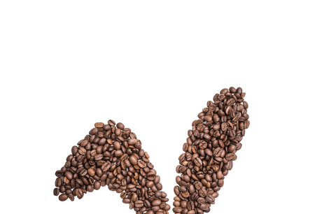 Easter holiday background with bunny ears made of freshly roasted coffee beans on a white background. Creative easter concept. Copy space.