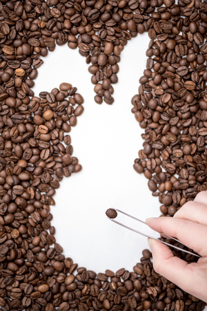 Female hand with tweezers laying out coffee beans and creates the shape of an Easter bunny. Creative concept
