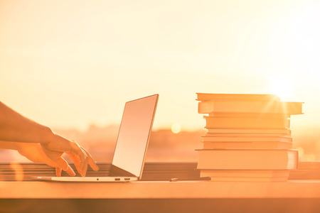 Female student with a lot of books and laptop preparing for university exam late evening on the sunset town background. Education concept Stok Fotoğraf