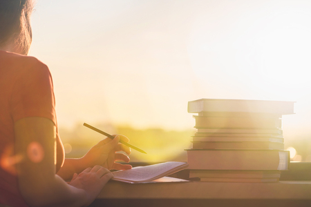 Female student with a lot of books preparing for university exam late evening on the sunset town background. Education concept