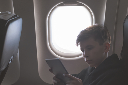 Caucasian boy fasten seat belt and using tablet pc and taking picture during air flight.  Safety travel with kid. concept
