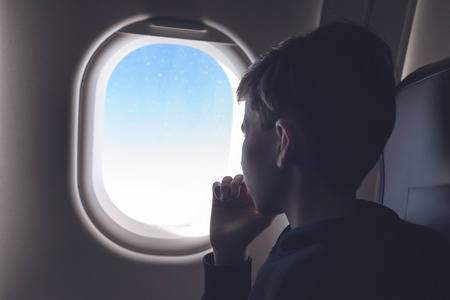 A boy have flight looking in the airplane window or porthole.