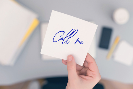 Woman clerk in the office holding paper sticker with the word call me. concept