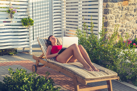 Woman freelancer with laptop in the swimsuit working on the lounger in her garden on the sunset.