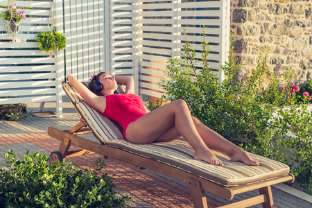 Girl in the headphones and swimsuit lies on the sunbed in her garden on the sunset.