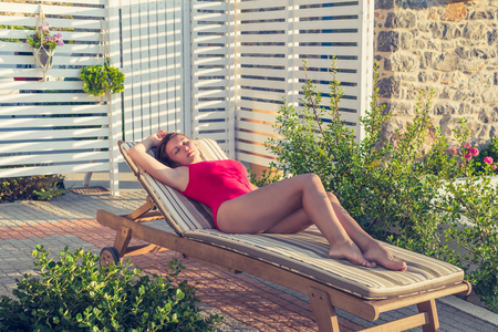 Girl in the swimsuit lies on the sunbed in her garden on the sunset.