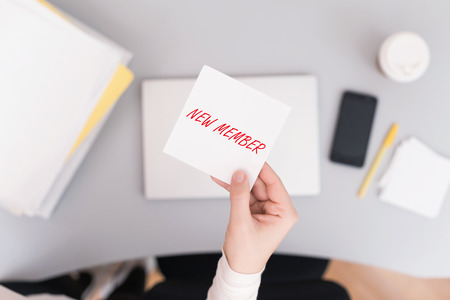 Woman clerk sitting holding note paper sticker with new member phrase. Business concept. Concept.
