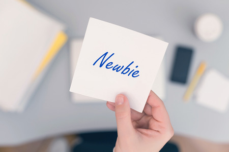 Woman clerk sitting holding note paper sticker with newbie word. Business concept. Concept.