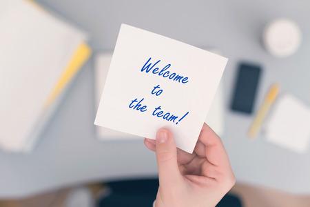 Impiegata donna seduta con adesivo di carta per appunti con frase di benvenuto alla squadra. Concetto di affari. Concetto.