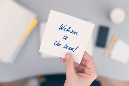Secretaria de mujer sentada sosteniendo una nota adhesiva de papel con la frase de bienvenida a la frase del equipo. Concepto de negocio. Concepto.