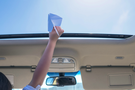 A girl is launching a paper airplane from open hatch of the car during summer vacation. Travel and freedom concept