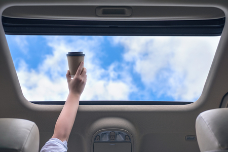 Girl passenger holding paper cup of coffee in open hatch of a car. Travel concept 版權商用圖片