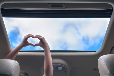 girl traveling by car and holds her hands in the form of heart out from open hatch of a vehicle. Travel lifestyle concept 免版税图像