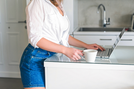 Girl with laptop with cap of coffee on the kitchen. Working home concept