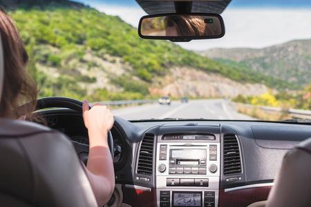 La ragazza sta guidando su strada a Tenerife, Isole Canarie. Vista dal sedile posteriore dell'auto sul parabrezza, sulla strada e sul conducente Archivio Fotografico