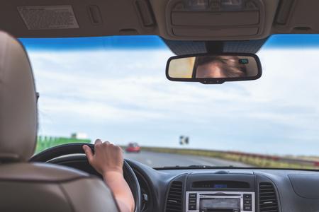 La fille conduit sur l'autoroute en Californie, aux États-Unis. Vue depuis la banquette arrière de la voiture sur le pare-brise, la route et le conducteur Banque d'images