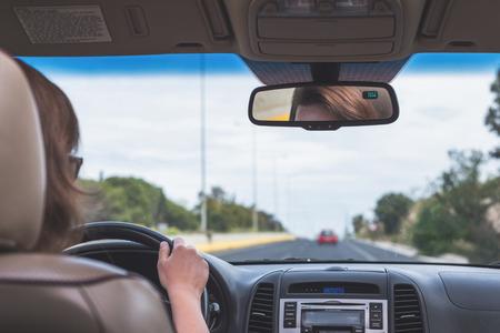그 소녀는 포르투갈의 고속도로에서 운전하고 있습니다. 앞 유리, 도로 및 운전자의 자동차 뒷좌석에서 보기 스톡 콘텐츠