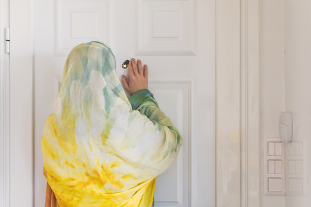 muslim woman in a colorful scarf looking on peephole door when somebody rings the doorbell