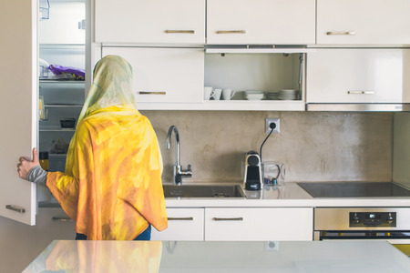 Back view on a muslim woman in a scarf opening door of a fridge on the kitchen. Preparation of breakfast Imagens