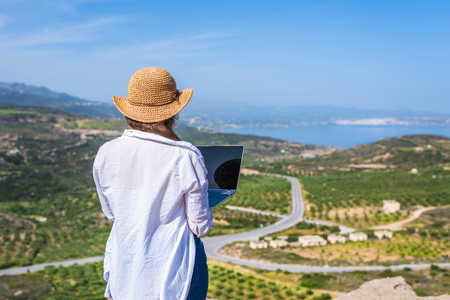 Woman freelancer in tourist clothes and straw hat with a laptop on top of a mountain. Concept Stok Fotoğraf