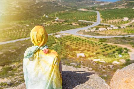 Een eenzame moslimvrouwenreiziger in een kleurrijke sjaal zit bovenop een berg. Stockfoto