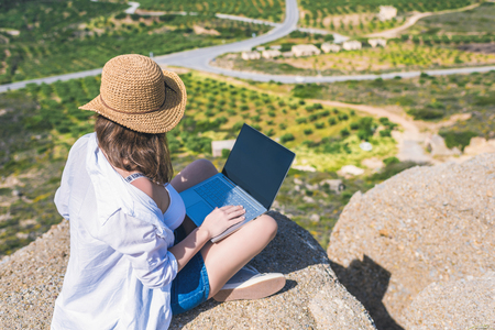 Woman freelancer in tourist clothes and straw hat with a laptop on top of a mountain. Concept 版權商用圖片